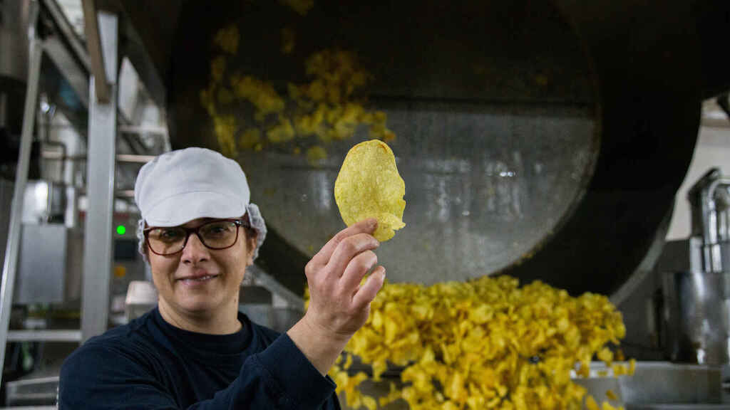Herminia, empleada de Monti, mostrando una patata recién salida del perol.