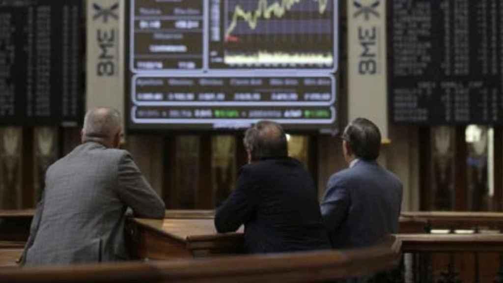 Varios inversores contemplan pantallas de negociación en la Bolsa de Madrid.