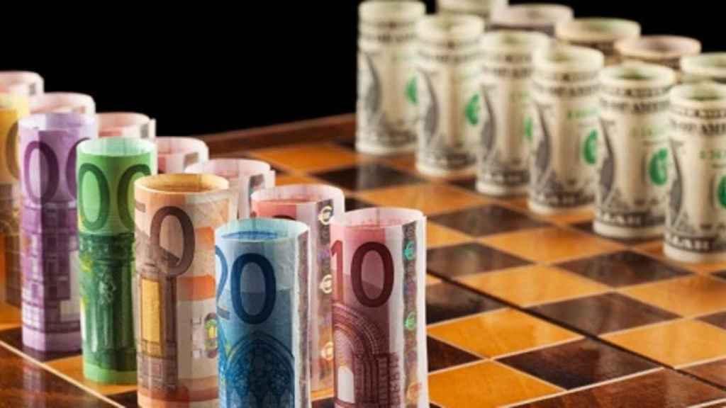 Biletes de euro y dólar en un tablero de ajedrez.