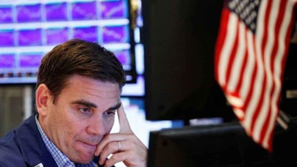 Un gestor mira una pantalla de cotización con gesto preocupado.