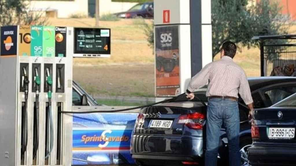 Un hombre echando gasolina a su vehículo en una estación de servicio.