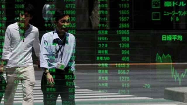 Dos ciudadanos pasan ante una pantalla de cotizaciones de la Bolsa de Tokio.