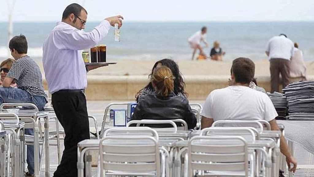 Un camarero sirviendo a unos clientes en una playa.