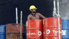 Un operario con barriles de petróleo en una refinería.