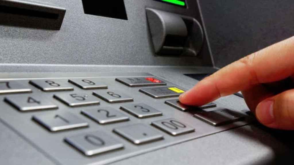 Un usuario de banca maneja un cajero automático.