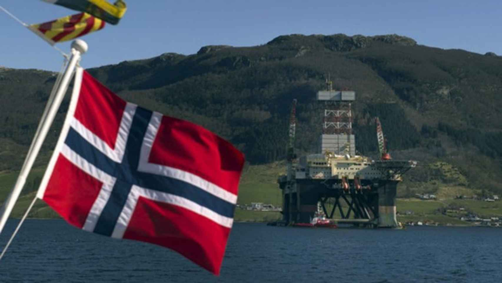 La bandera de Noruega frente a una plataforma petrolera.