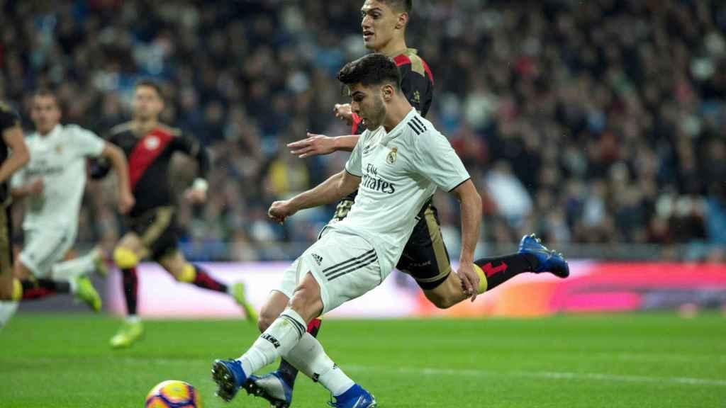 Marco Asensio pelea un balón con el defensa uruguayo del Rayo Vallecano, Emiliano Velázquez