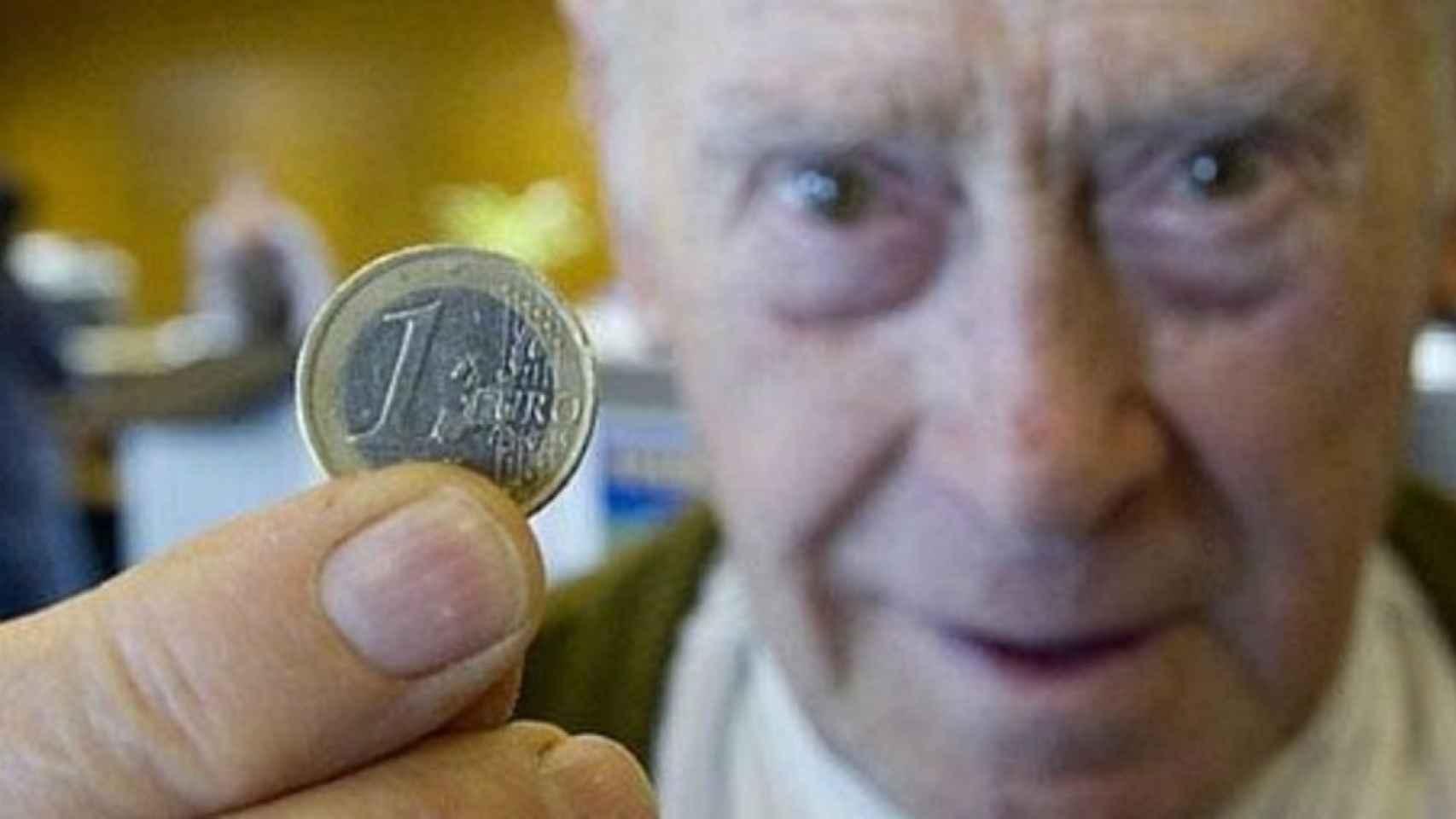 Un jubilado muestra una moneda de un euro.