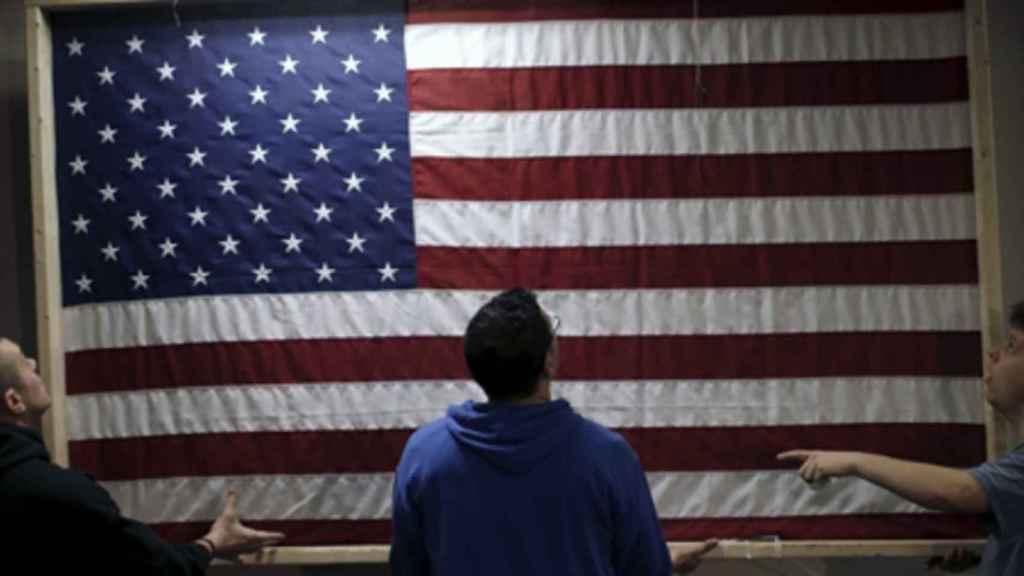 Unos jóvenes sostienen una bandera de EEUU.