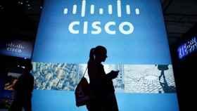 Una usuaria pasa por delante de una representación de Cisco.