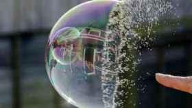 Una persona hace explotar una burbuja con el dedo.