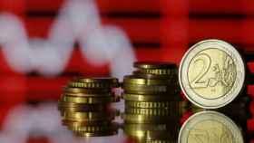 Monedas de euro sobre una gráfica bajista.