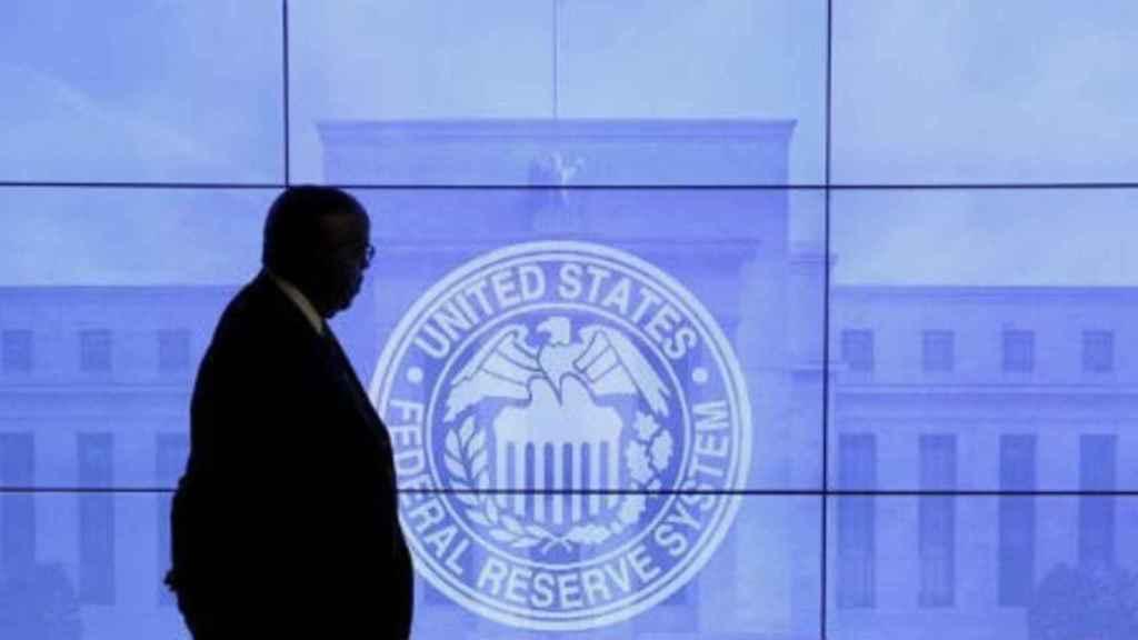 Un trabajador de la Reserva Federal pasa ante una representación del sello de la institución.