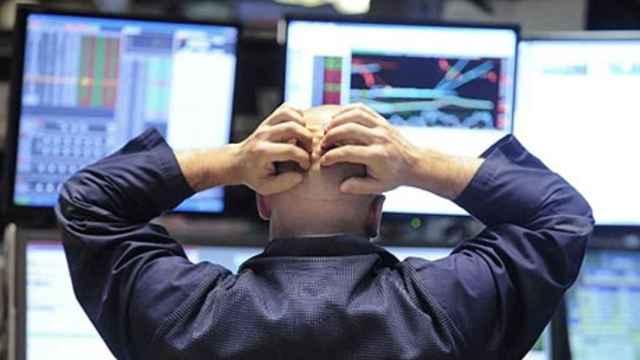 Un bróker con gesto de preocupación ante distintas pantallas de cotización.