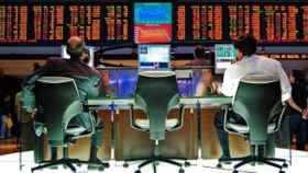 Traders ante una pantalla de bolsa en el parqué.