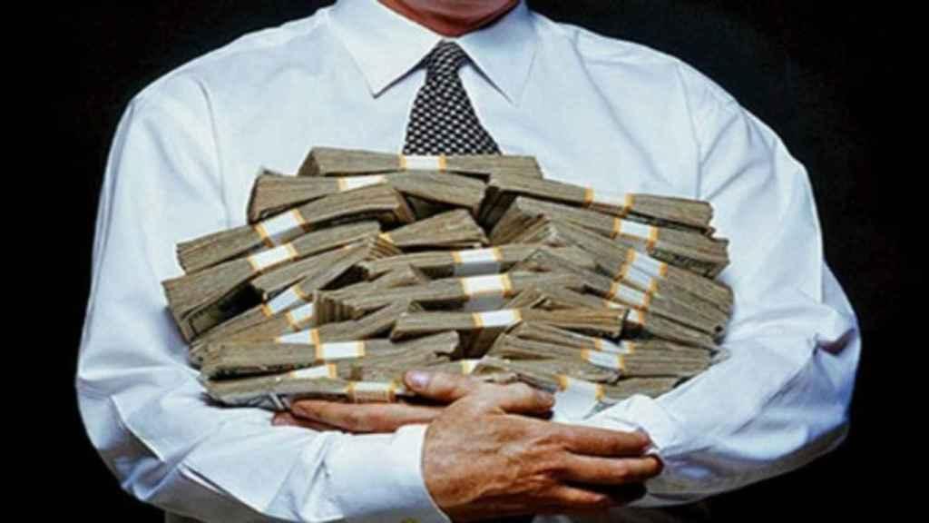 Un hombre con corbata sostiene fajos de billetes.
