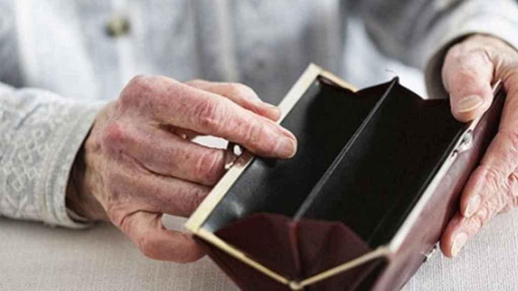 Un jubilado muestra una cartera vacía.