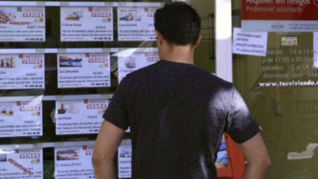 Imagen de una persona frente al escaparate de una inmobiliaria.