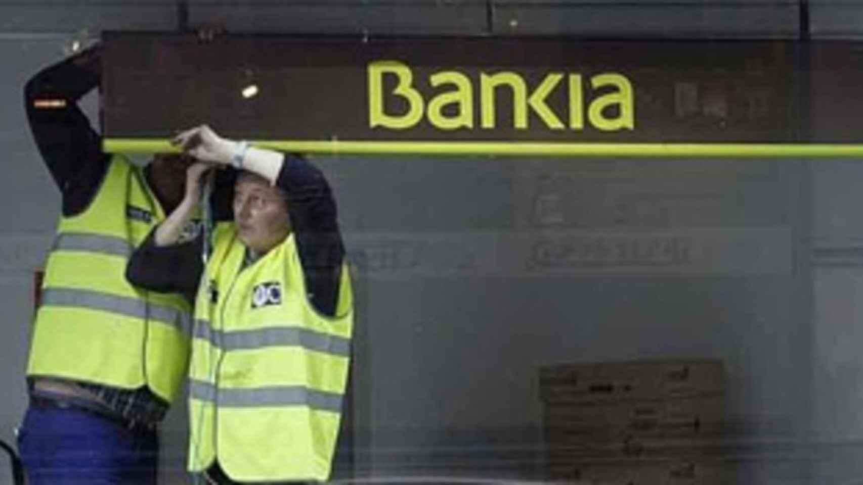 Unos operarios fijan un rótulo en una sucursal de Bankia.