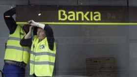 Empleados retirando un cartel de Bankia.
