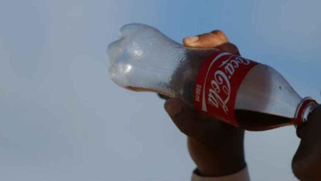 Una persona refrescándose con una botella de Coca-cola.