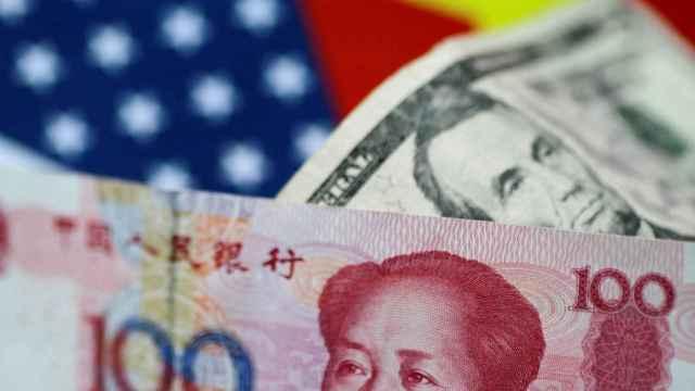 Dos billetes de yuan y dólar sobre banderas de EEUU y China.