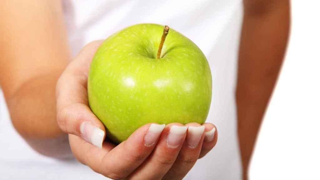 Una hermosa manzana verde que va a provocar una explosión de sabor en la boca de la mujer que la sostiene.