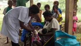 Una de las enfermeras poniendo una vacuna a un niño de Vanuatu.
