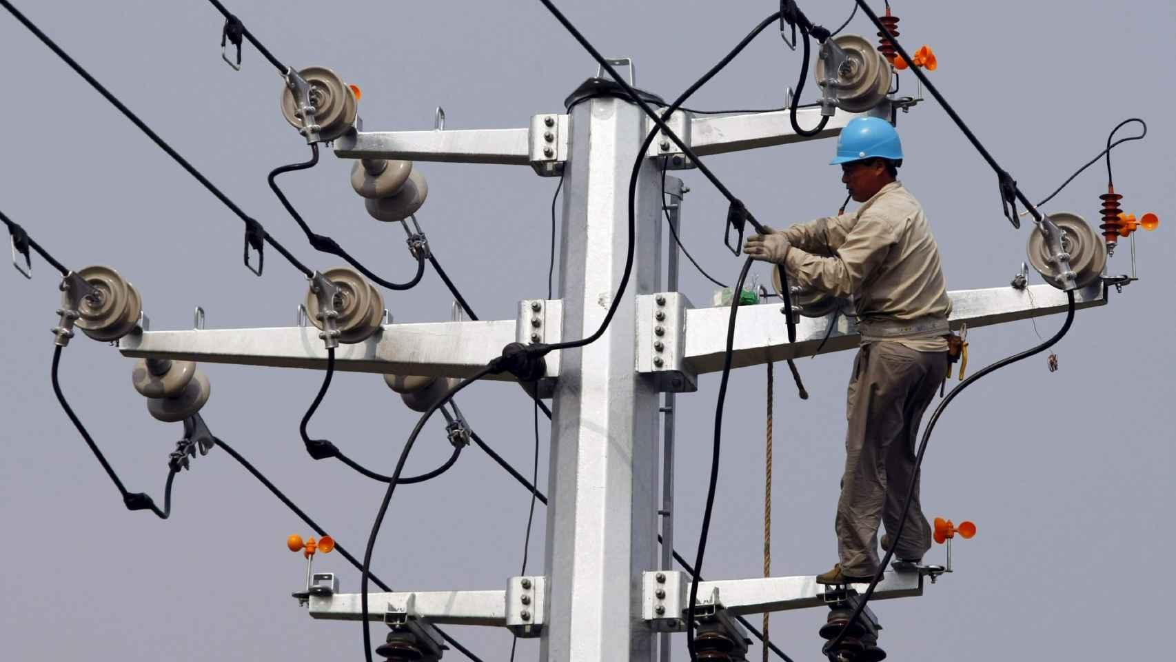 Un operario trabaja en una torre de electricidad, en una imagen de archivo.