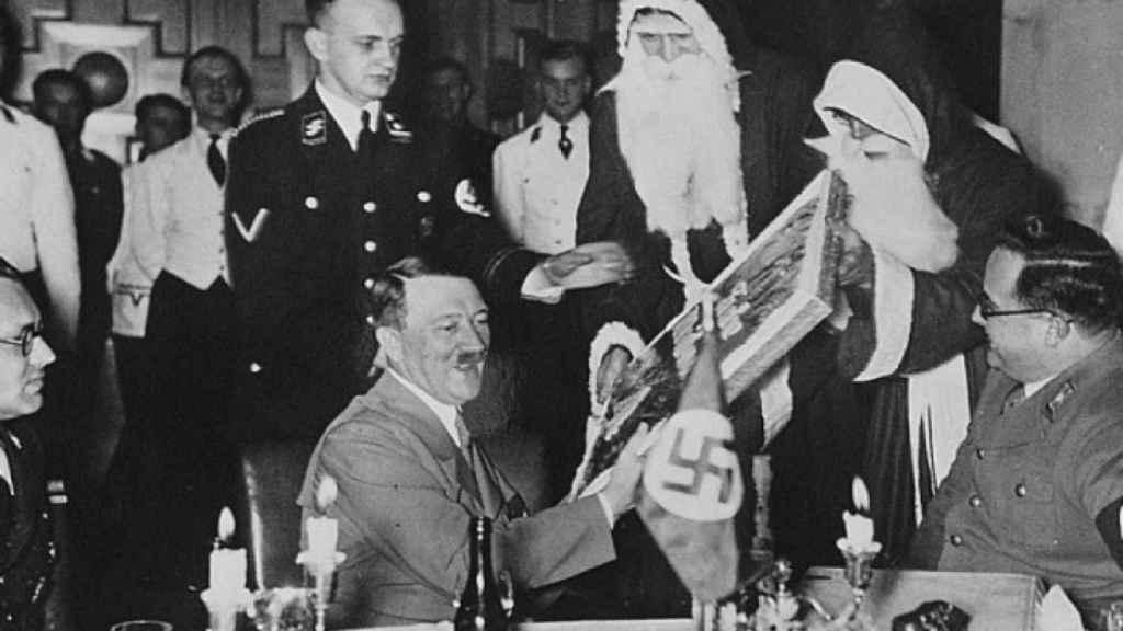 Adolf Hitler y dos nazis disfrazados de Papá Noel durante una cena de Navidad.