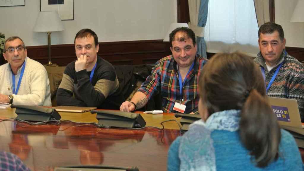 Trabajadores de subcontratas mineras reunidos con los diputados de Podemos en una sala del Congreso.