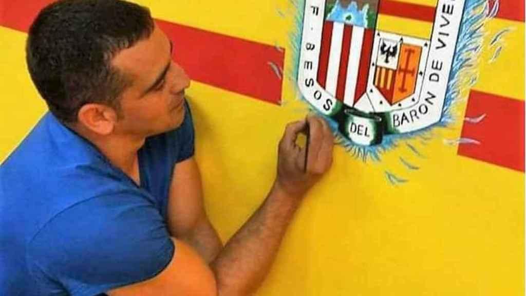 Edu Colmena pintando el escudo del equipo de fútbol de su barrio