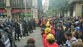 Agentes de la Brimo frente a un cordón de bomberos en la calle Fusteria.