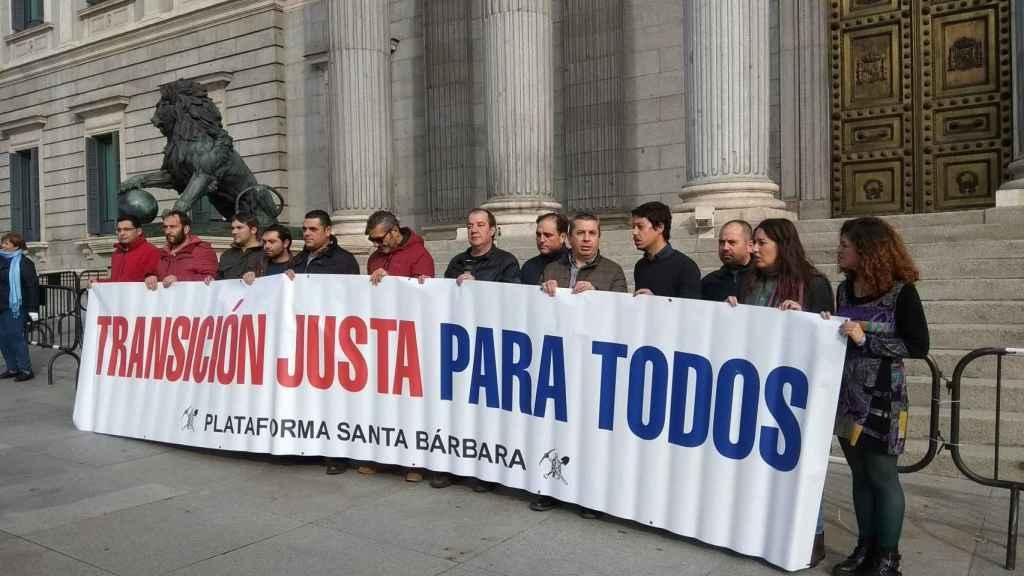 Diputados de Podemos, junto a trabajadores de subcontratas mineras, ante las puertas del Congreso.