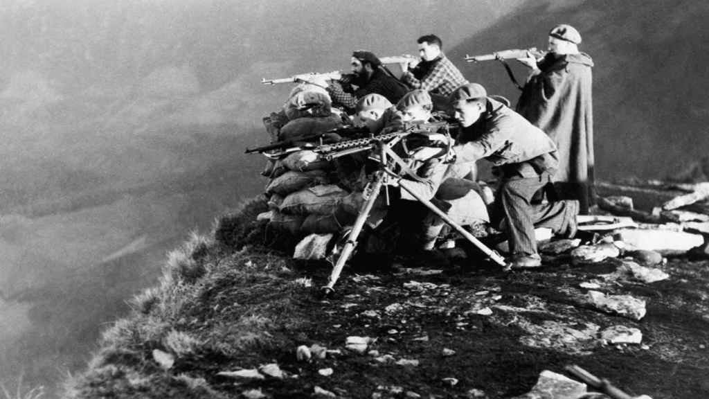 Soldados franquistas apuntan al horizonte con fusiles y una ametralladora MG 13 de fabricación alemana.