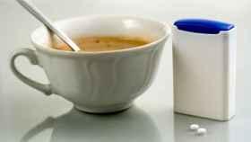 Una taza de café junto a un tarrito con sacarina.