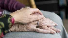 Una hija posa su mano sobre la mano de su madre anciana.