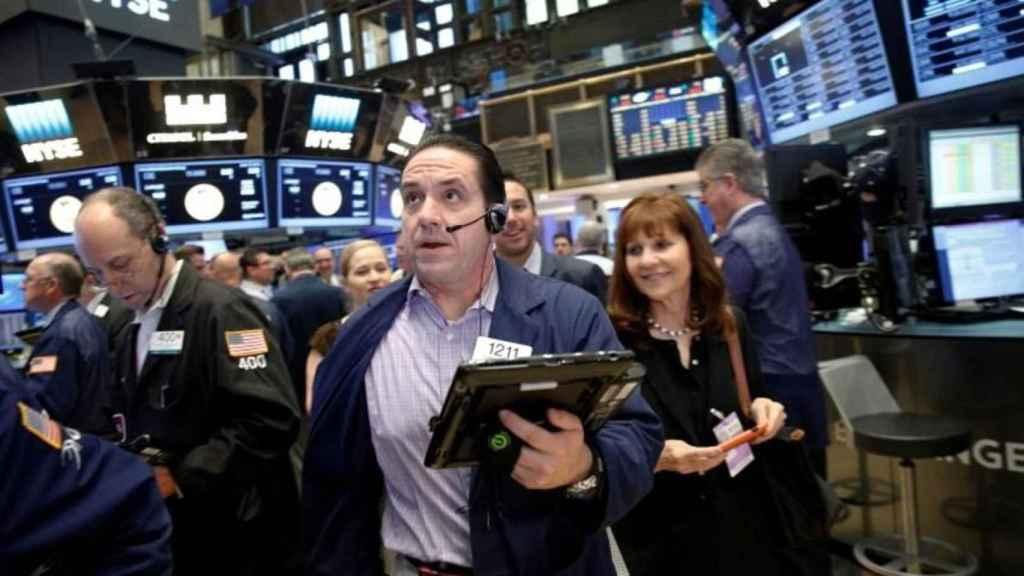 Varios brókeres con gesto entusiasta en la Bolsa de Nueva York.