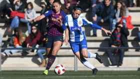 Dos jugadoras del FC Barcelona femenino y del RCD Espanyol femenino disputan un balón