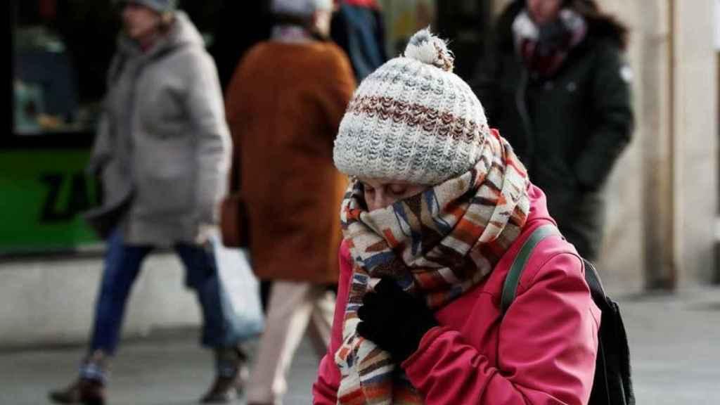 Una mujer se protege del intenso frío en Pamplona.