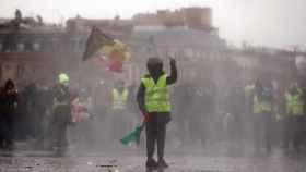 Un manifestante de los 'chaleco amarillos' se enfrenta a la Policía en las inmediaciones del Arco del Triunfo, en París.