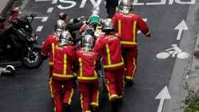 Bomberos asisten a una víctima en la calle de la explosión.