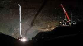 Varios operarios viendo la obra. A la dcha., la cápsula en la que los mineros descenderán.