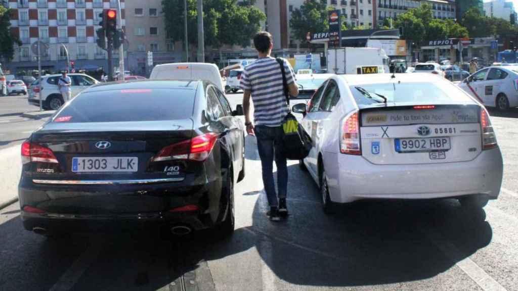 Un ciudadano entre una VTC y un Taxi en Madrid.