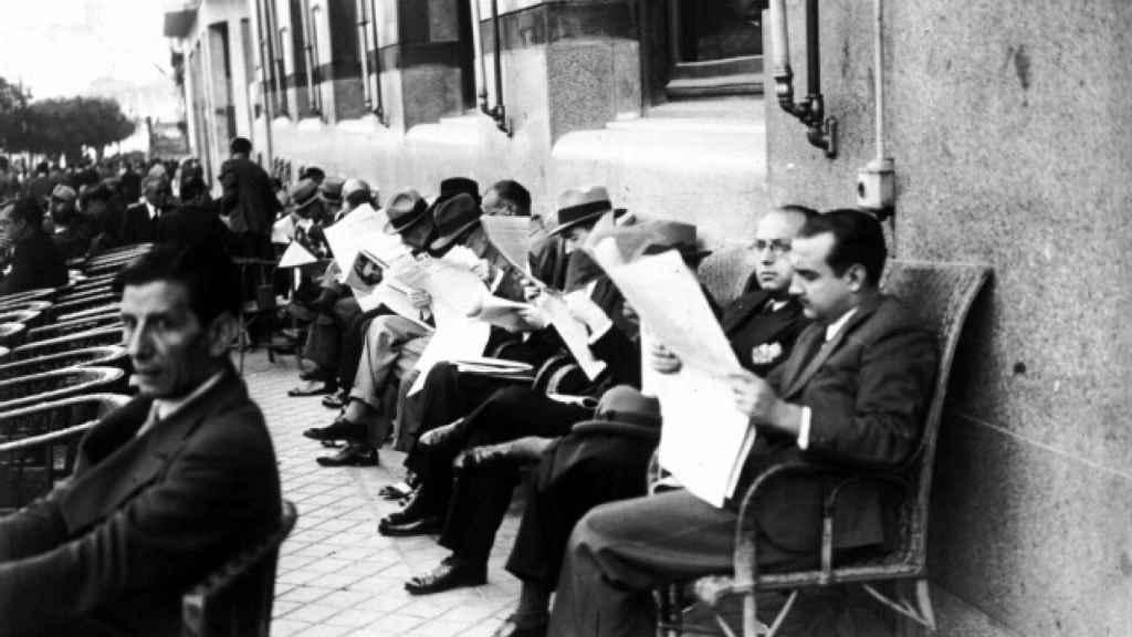 Un grupo de hombres lee el periódico en la terraza del Círuclo de Bellas Artes de Madrid.