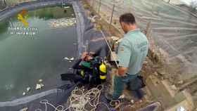 Agentes de la Guardia Civil preparándose para sumergirse en una balsa