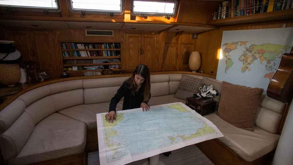 Paula consultando las cartas naúticas en el interior del velero.