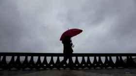 Una mujer camina bajo la lluvia por el paseo marítimo de A Coruña.