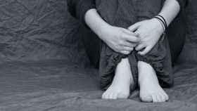 Un adolescente se abraza las piernas.