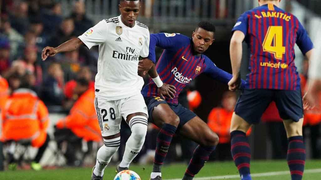 Vinicius controla un balón junto a dos jugadores del FC Barcelona